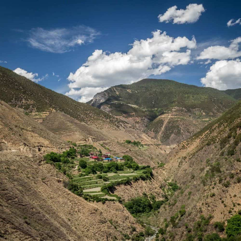 Green fields of barley and Tibetan village in dry barren valley Sichuan China