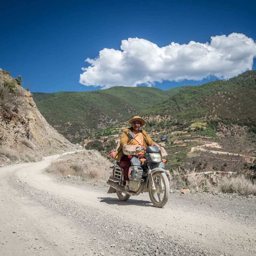 A Tibetan monk on a motor bike on gravel in Sichuan China
