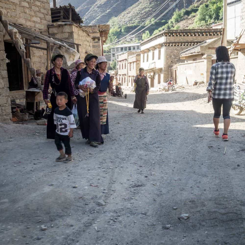 Tibetan ladies in dusty village street in Sichuan China