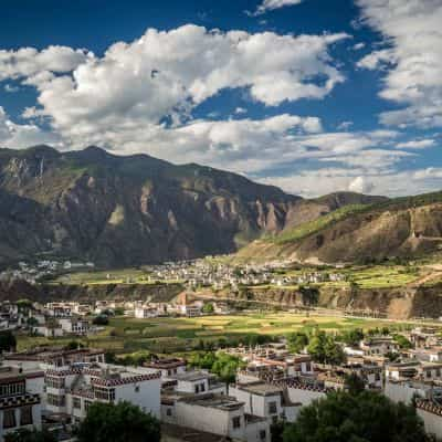 View of green valley and white houses in Sichuan China Eastern Tibet