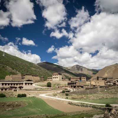 Traditional Tibetan houses blue sky and green valley in Sichuan China