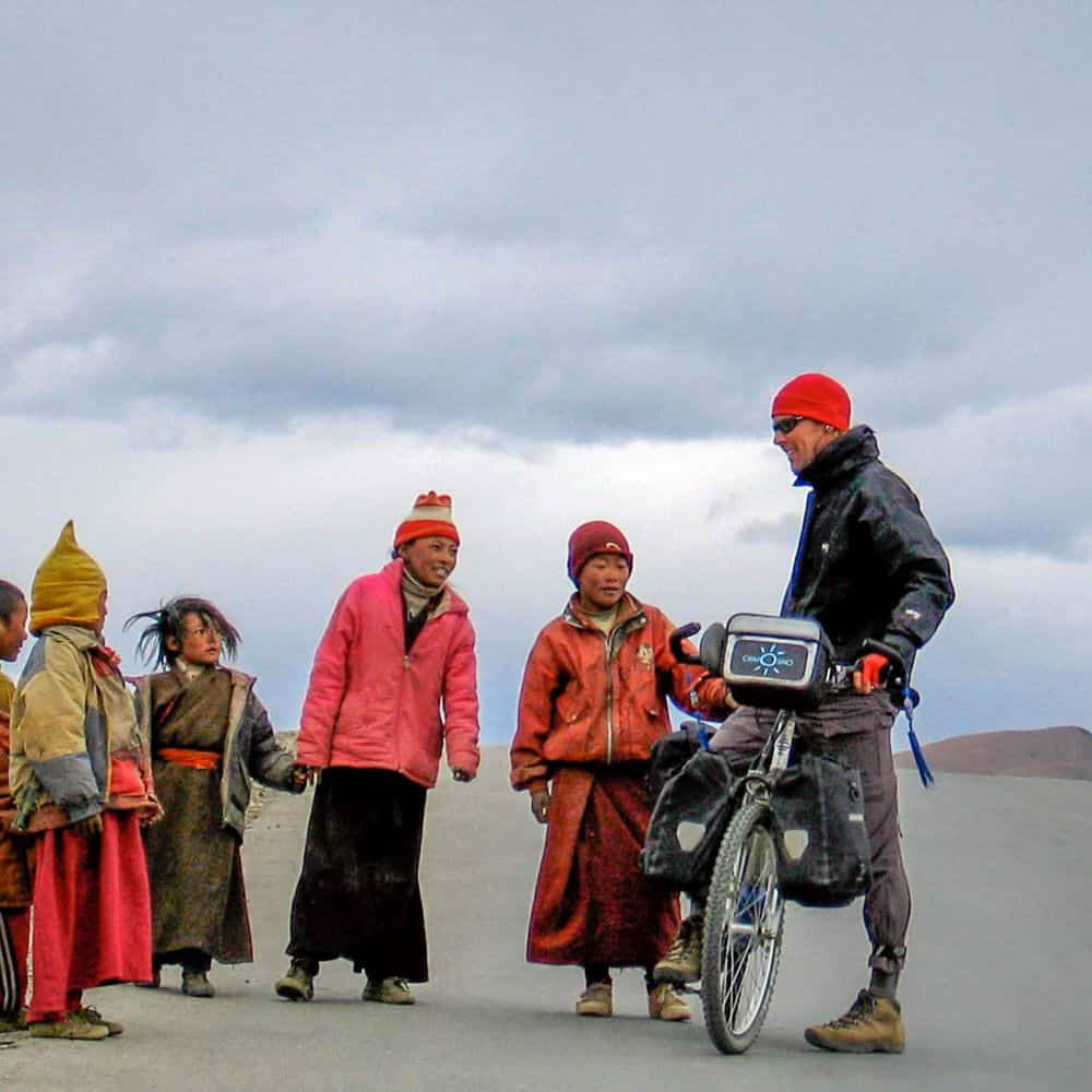 Adventure cyclist and Tibetan children on a high pass in Sichuan Province China