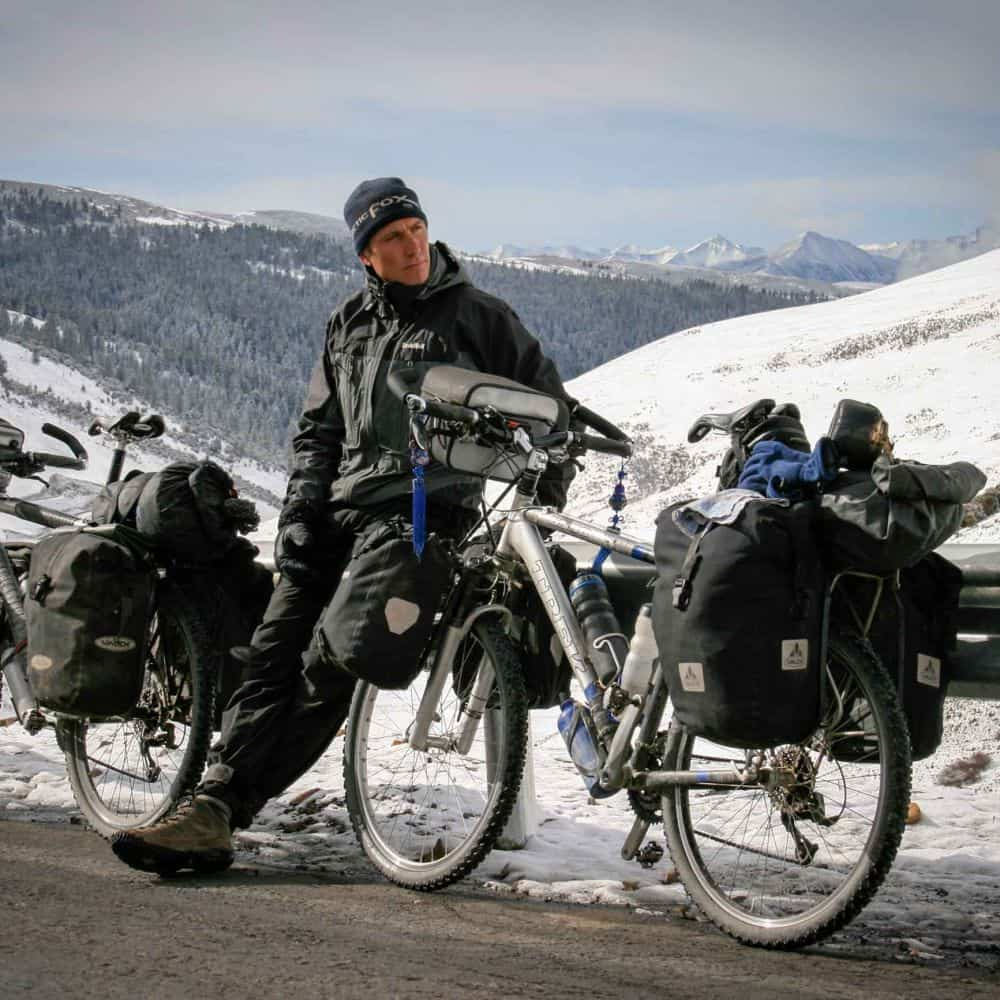 An adventure cyclist with his bike and snowy background Sichuan China
