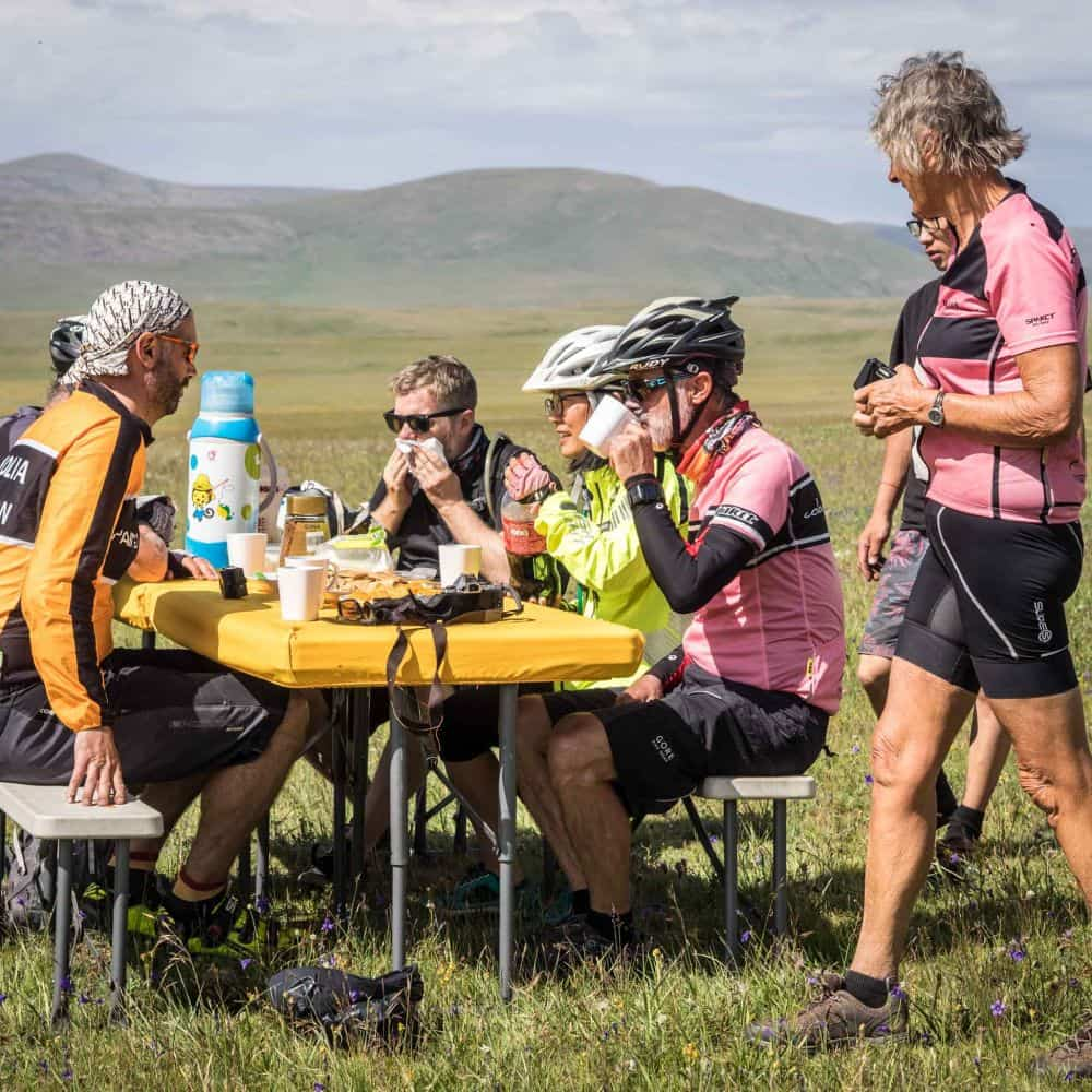 Cyclists eating in the Mongolian wilderness