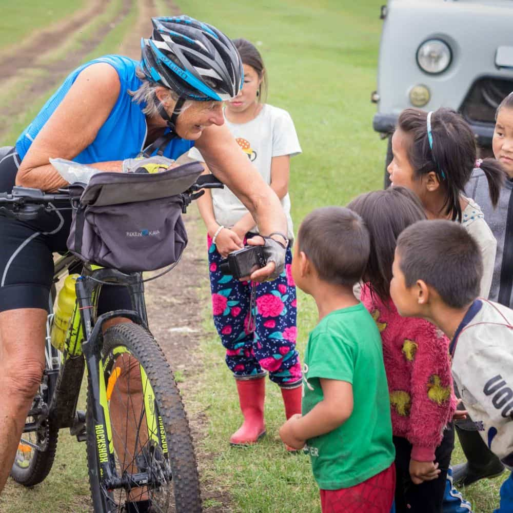 A lady meets local kids whilst cycling through Mongolia