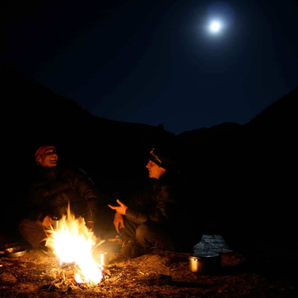 Cyclists by camp fire cycling through eastern Tibet Sichuan China