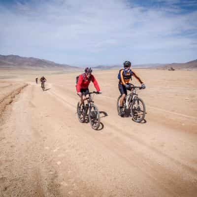 Cyclists riding across a desert in Mongolia