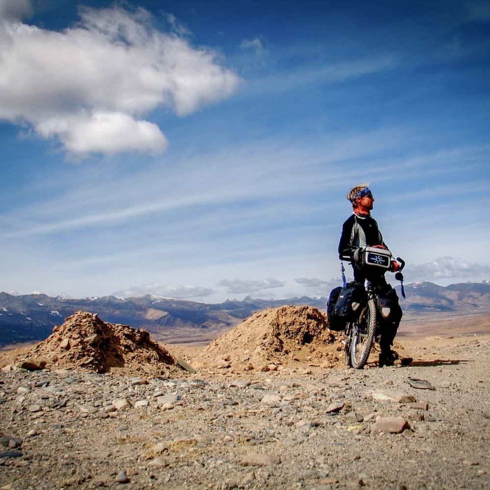 A cyclist on a high gravel pass in Sichuan China