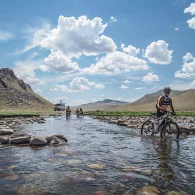 cyclists crossing a river in Mongolia
