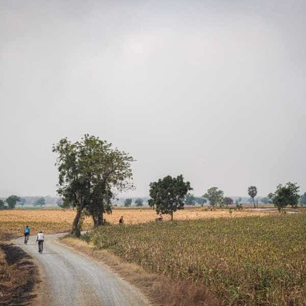 Group of gravel cyclists on grey gravel road in Thailand