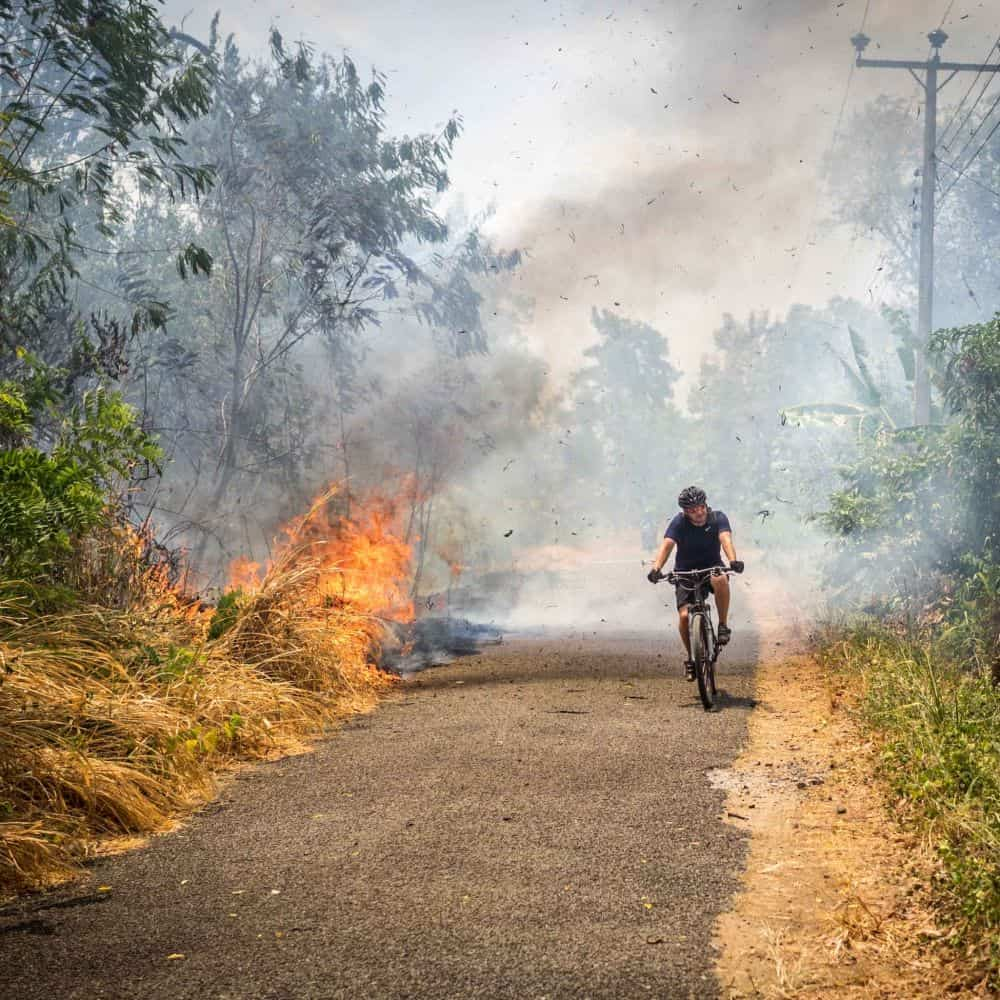 Cyclist riding past fire whilst touring in Sri Lanka