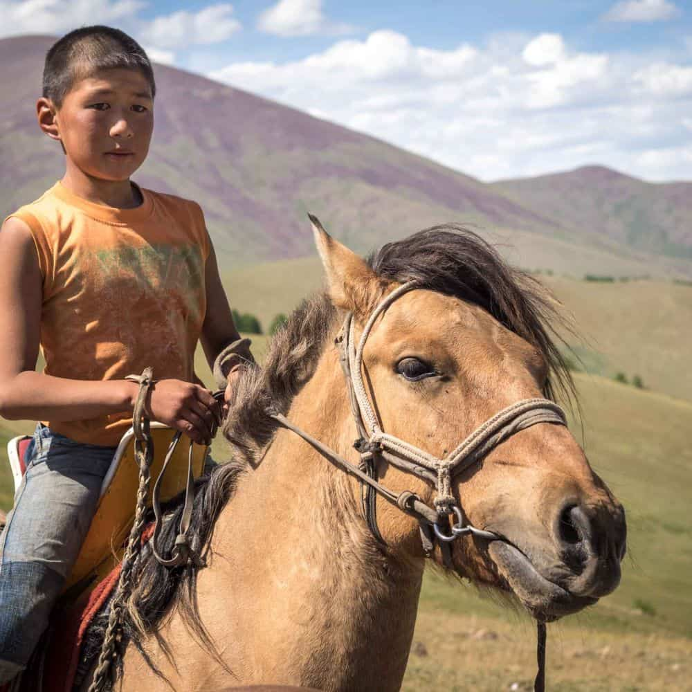 Mongolian boy on horse back