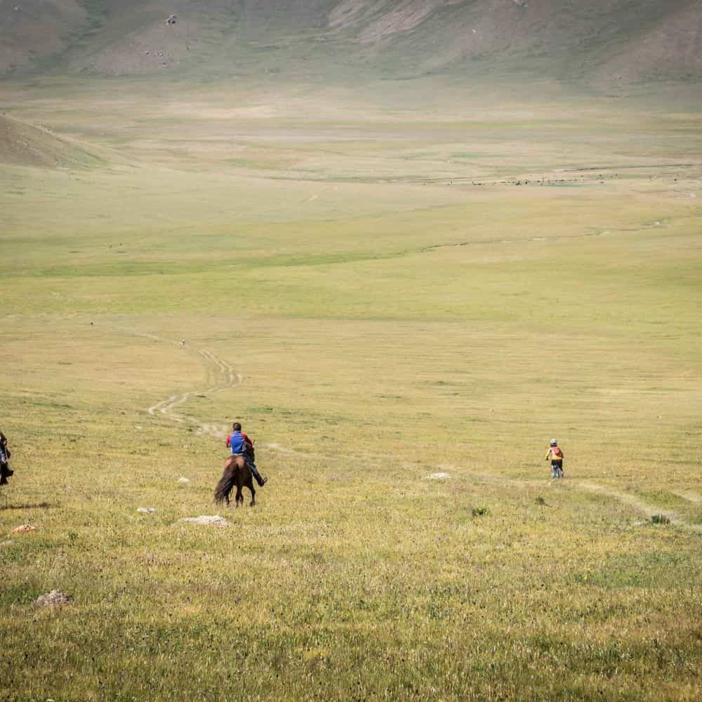Horse men and cyclist in Mongolia