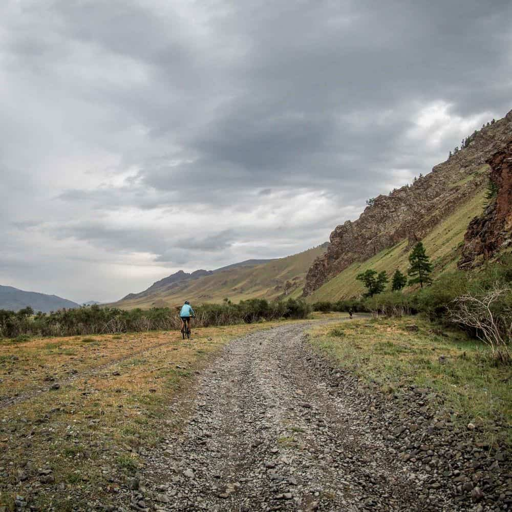 A lone cyclists on gravel road beneath a moody sky in Mongolia