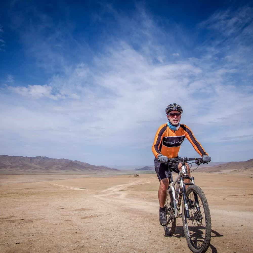 Cyclist in Mongolian desert beneath blue sky