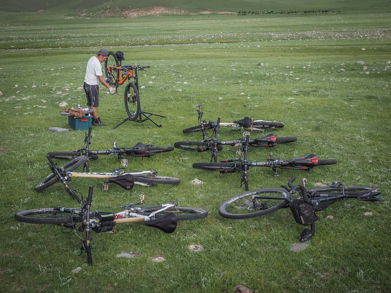 a bicycle mechanic working on bikes whilst camping in mongolia
