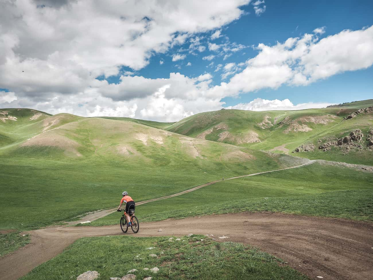 a cyclist on a hilly gravel road in Mongolia