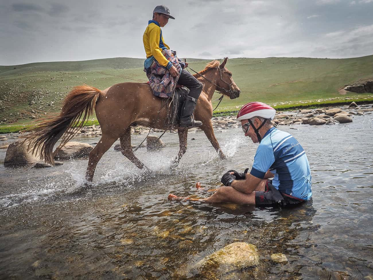 a cyclist in Mongolia sitting in a river as a horse rider passes by