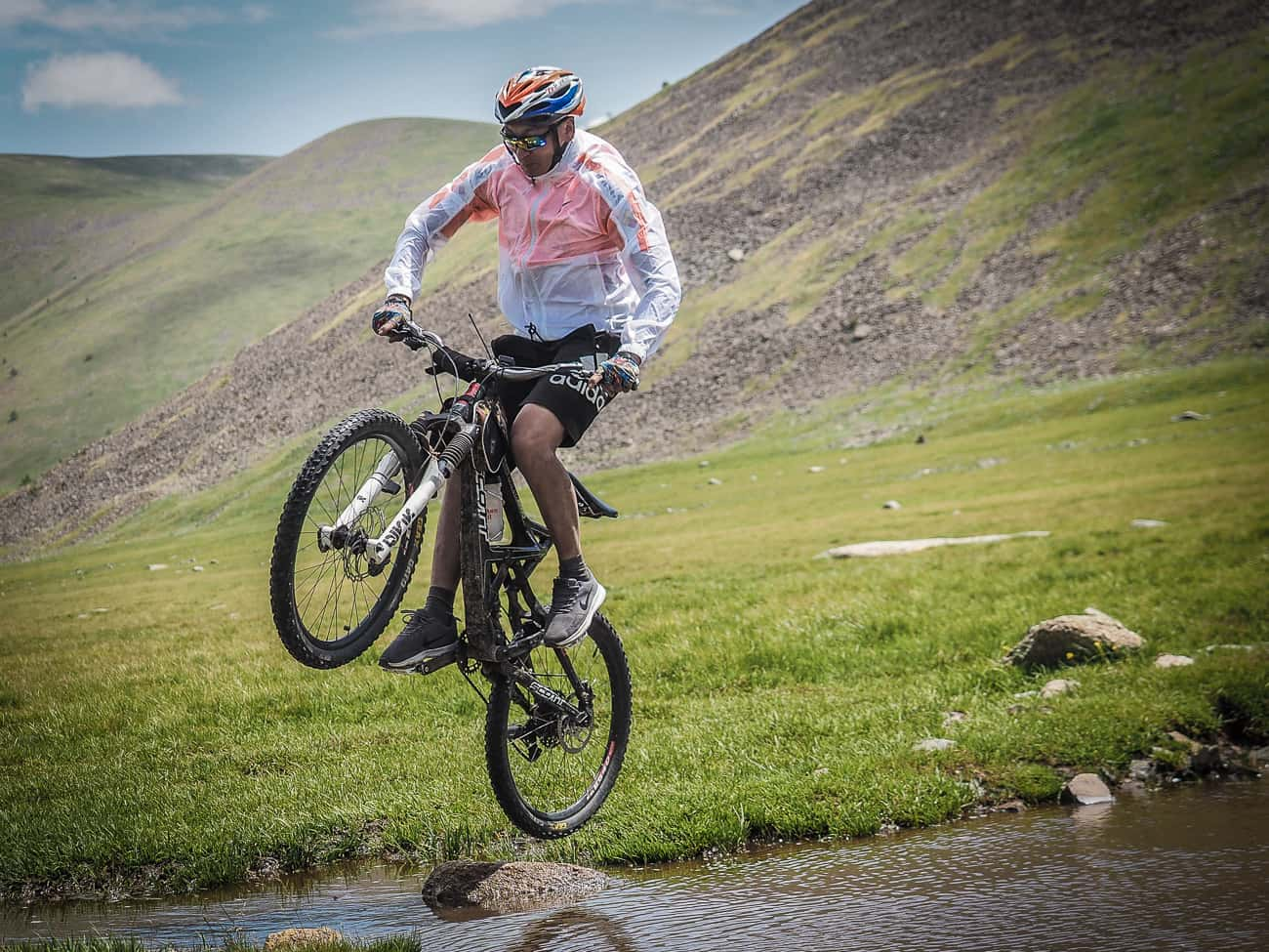 a Mongolian mountain biker jumping a stream