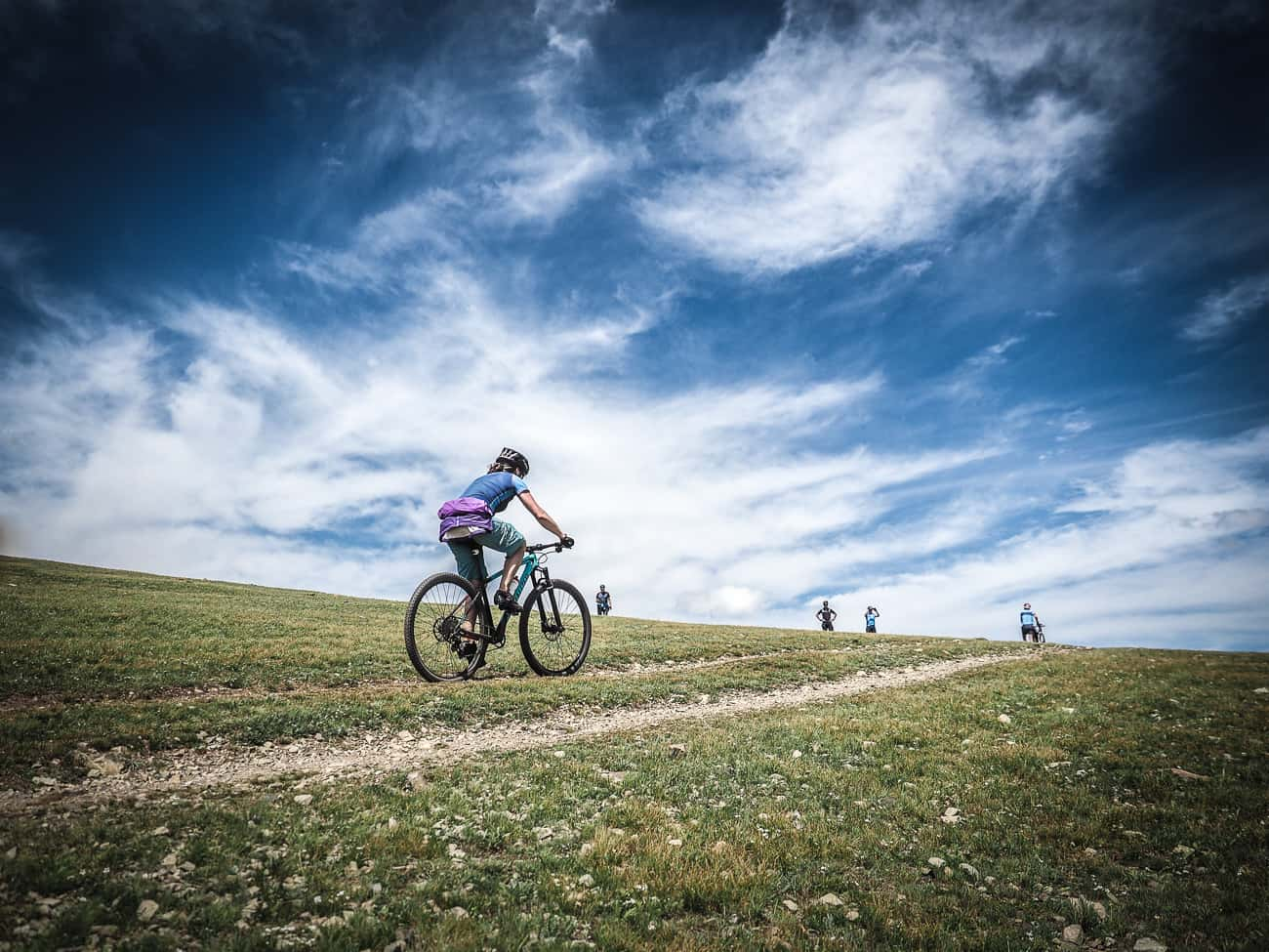 cyclists in Mongolia riding a gravel track up hill beneath a blue sky