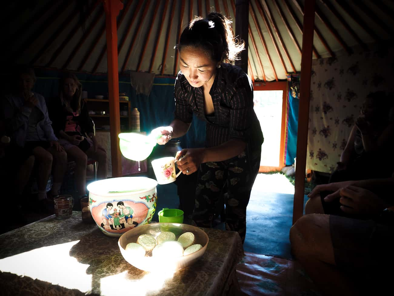 a Mongolian lady offers cyclist food and drink inside her ger