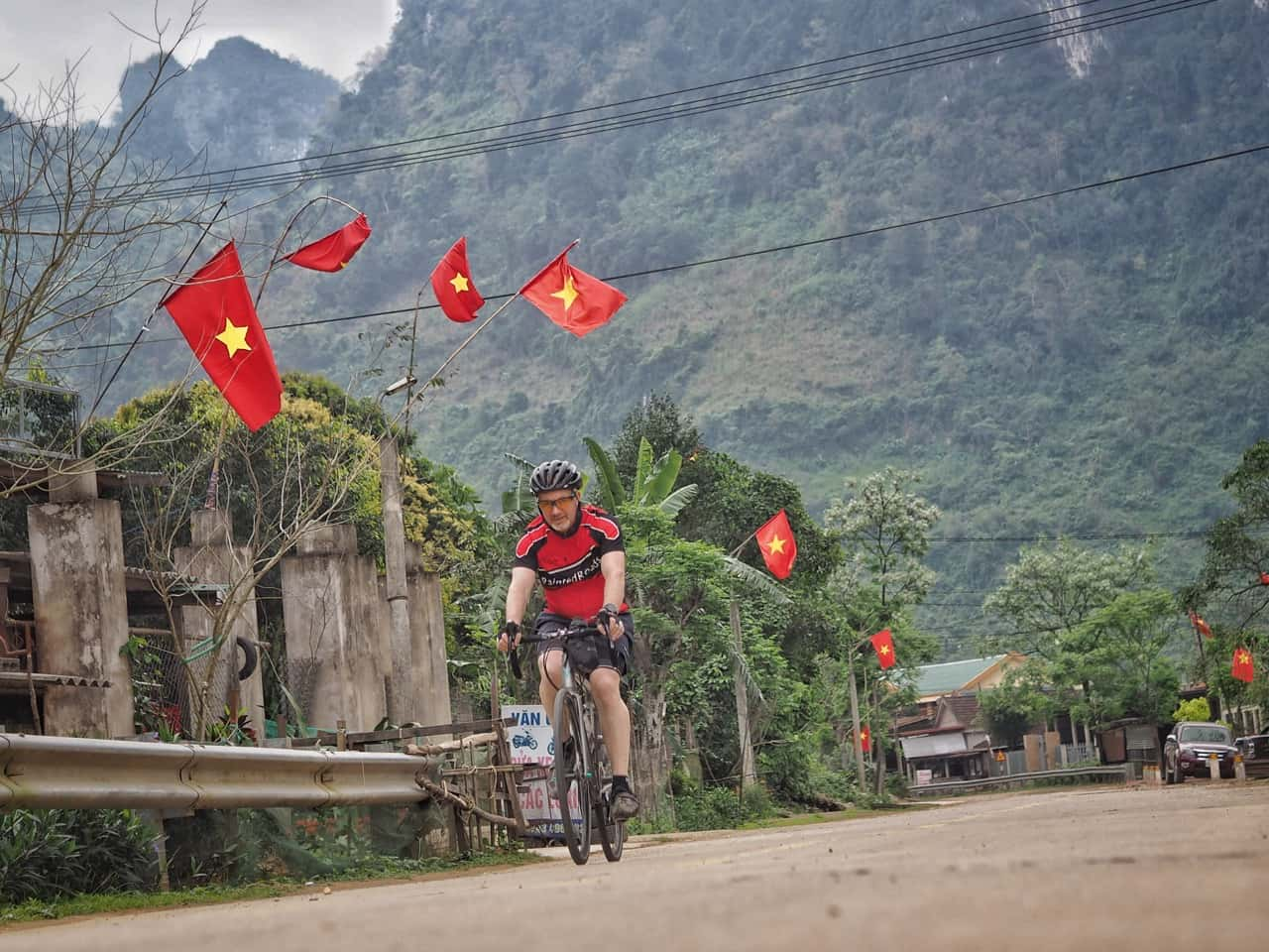 cyclist touring vietnam beneath vietnamese flags