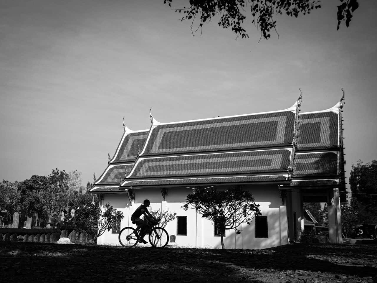 gravel cyclists passing old temple in Thailand black and white image