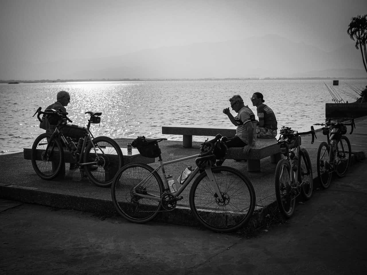 black and white image of gravel cyclists resting by a lake during Thailand bike packing ride